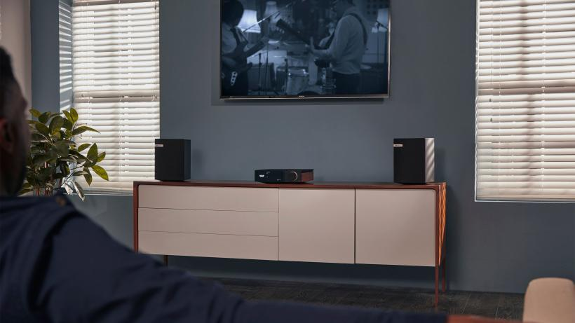 Man watching TV with Evo and speakers