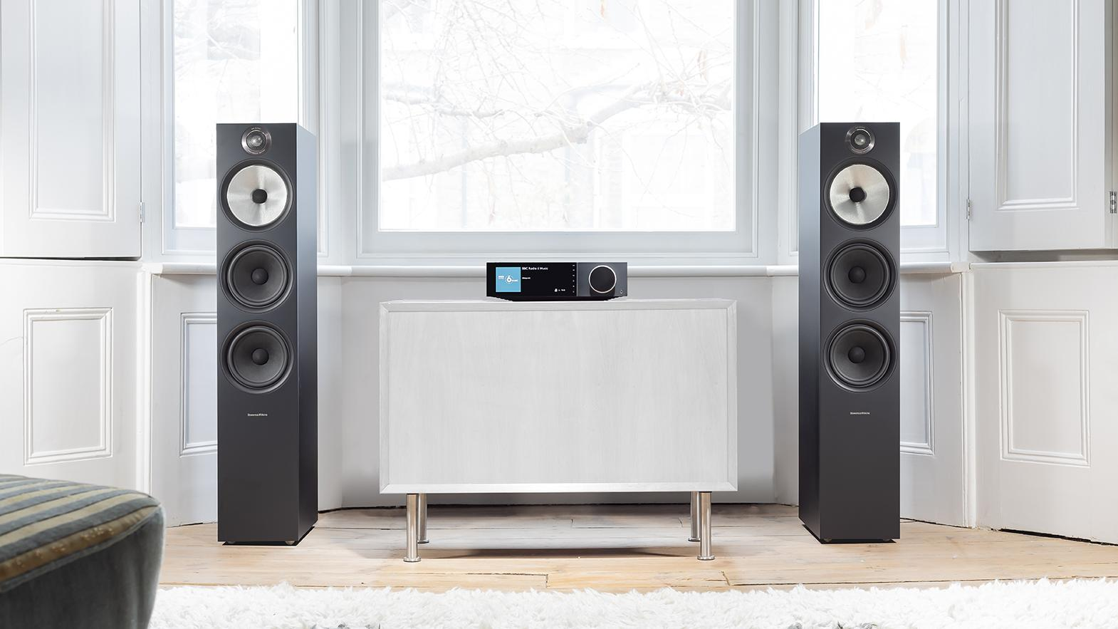 Evo 150 and tower speakers in white living room