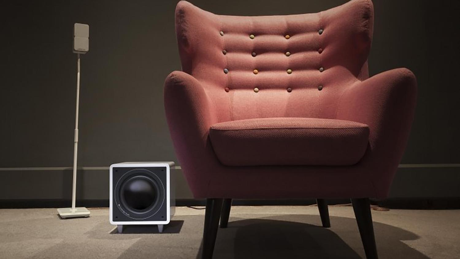Minx X301 300W subwoofer next to red arm chair